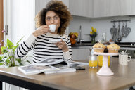Woman sitting in kitchen, reading magazines and drinking coffee - FMOF00599
