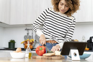 Woman standing in kitchen, preparing salad for lunch - FMOF00605