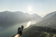Austria, Tyrol, Legs of a man, watching paraglider over lake Achensee - WFF00083