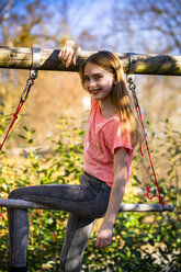 Portrait of smiling girl sitting on gymnastic bar in the garden - SARF04234