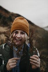 UK, Scotland, Highland, portrait of happy young woman holding fern - LHPF00595