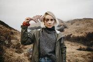 UK, Scotland, Highland, portrait of young woman holding fern - LHPF00601