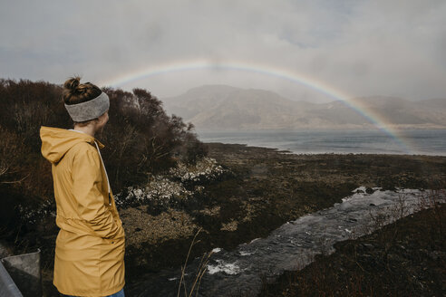 UK, Scotland, Highland, woman looking at rainbow above the sea - LHPF00613