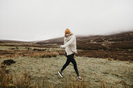 UK, Scotland, Isle of Skye, happy young woman running in rural landscape - LHPF00616