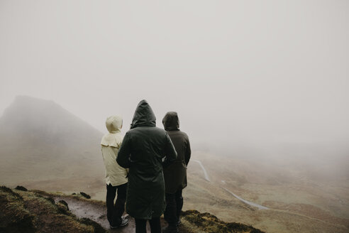 UK, Scotland, Isle of Skye, Quiraing Viewpoint, rear view of three women in foggy landscape - LHPF00622