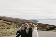 UK, Scotland, Highland, happy female friends on a road at the coast - LHPF00652