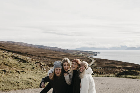 UK, Scotland, Highland, happy female friends on a road at the coast - LHPF00652