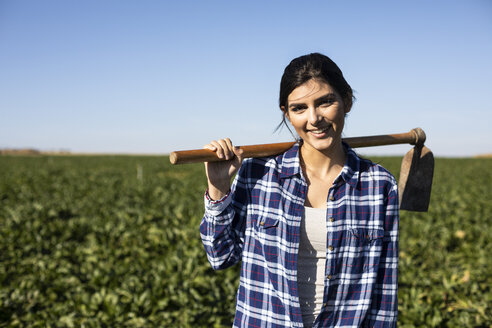 Young woman farmer with hoe on field - ABZF02322
