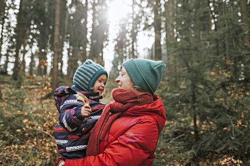 Mother carrying happy little daughter in autumnal forest - DWF00410