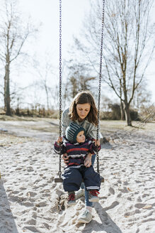 Mother with little daughter on swing on a playground - DWF00413