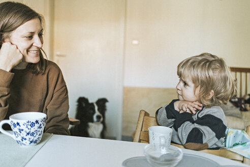 Smiling mother and daughter sitting at table at home with dog in background - DWF00419