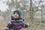 Toddler girl in warm clothes at a fence in forest - DWF00422