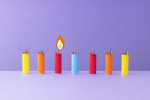 Multiple lighters organized in a row over blue background. - DRBF00149