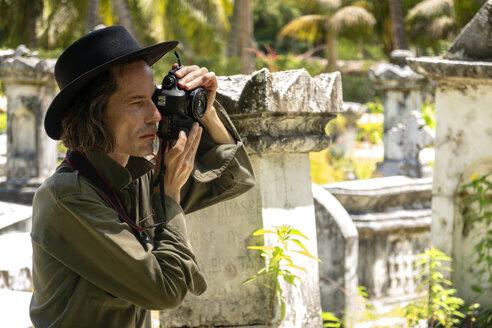 Fotograf, Fotokünstler bei der Arbeit, Making Of, Mann mit Hut in den Tropen, Auf dem Friedhof der ersten französischen Siedler auf La Digue, Seychellen, Urlaub - NDF00893
