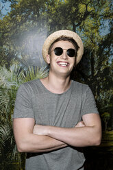 Young man wearing hat and sunglasses, standing in front of photo wallpaper, with arms crossed - PESF01561