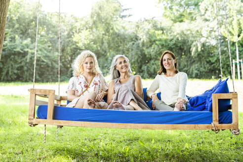 Women of a family relaxing in garden, sitting on a swing bed - PESF01606