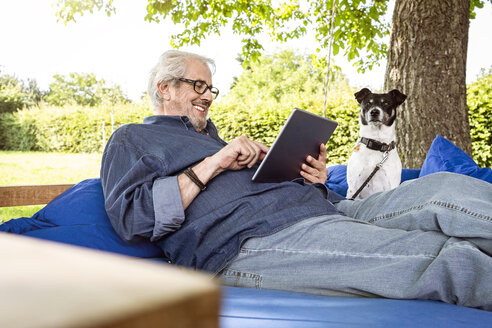 Senior man relaxing on a swing bed in his garden, using digital tablet - PESF01618