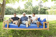 Men of a family sitting on a swing bed ing the garden, talking - PESF01621