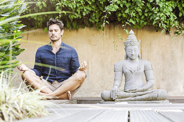 Man sitting cross-legged next to Buddha statue in a Zen garden, meditating - PESF01630