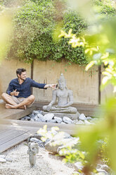 Man sitting cross-legged next to Buddha statue in a Zen garden, using smartphone - PESF01633