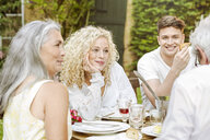 Happy family eating together in the garden - PESF01642