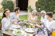 Happy family eating together in the garden, clinking glasses - PESF01645