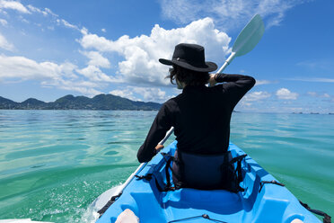 Seychelles, Mahe, back view of black dressed man with hat kayaking - NDF00912