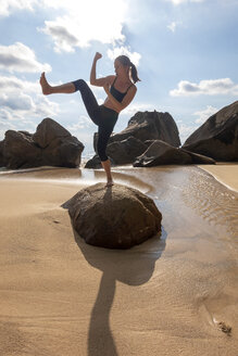 Seychelles, Mahe, Takamaka Beach, woman standing on a rock shadowboxing - NDF00915