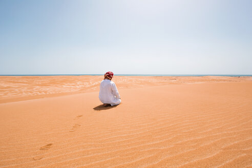 Bedouin in National dress praying in the desert, rear view, Wahiba Sands, Oman - WVF01316