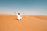 Bedouin in National dress sitting in the desert, raising arms, Wahiba Sands, Oman - WVF01319
