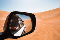 Mirror image of a man taking pictures from a off-road vehicle, Oman, Wahiba Sands - WVF01322