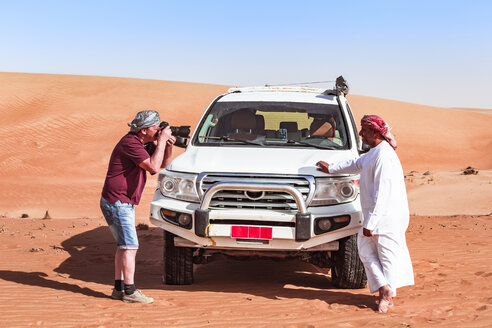 Tourist taking pictures of his local driver in the desert, Wahiba Sands, Oman - WVF01346