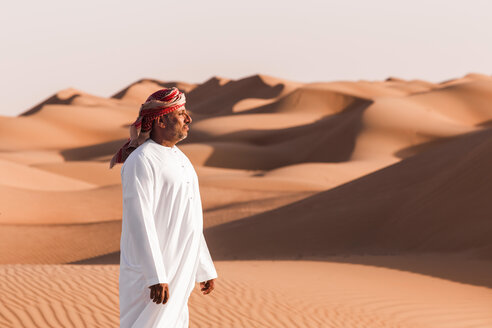 Bedouin in National dress standing in the desert, Wahiba Sands, Oman - WVF01379