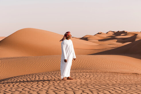 Bedouin in National dress standing in the desert, Wahiba Sands, Oman - WVF01382
