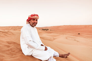 Bedouin in National dress sitting on sand dune in the desert, Wahiba Sands, Oman - WVF01409
