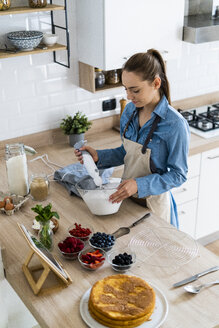 Young woman preparing a cream cake, using tablet - GIOF06183
