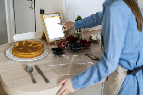 Young woman preparing a cake, using tablet - GIOF06195