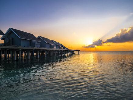 Malediven, Rasdoo-Atoll, Lagune einer Malediveninsel mit Sandstrand und Wasserbungalows in der Abenddämmerung - AMF06907