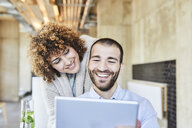 Happy man and woman sharing tablet in modern office - FMKF05557