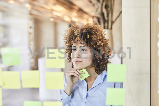 businesswoman brainstorming with post-its on glass pane - FMKF05566 - Jo Kirchherr/Westend61