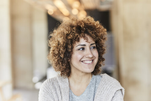Portrait of smiling woman with curly hair - FMKF05590