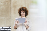 Smiling woman using tablet at concrete wall - FMKF05599