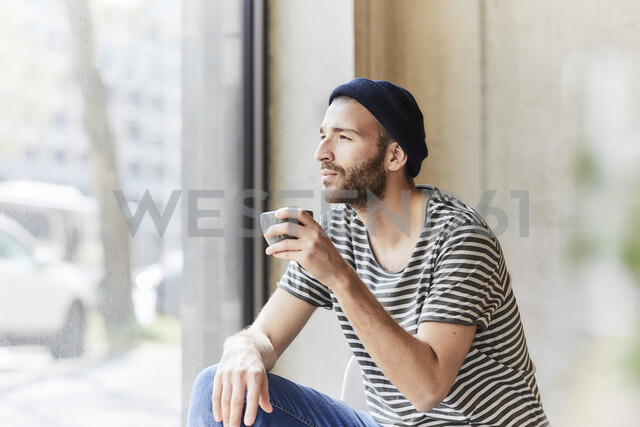 Young man holding coffee cup at the window - FMKF05608 - Jo Kirchherr/Westend61