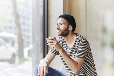 Young man holding coffee cup at the window - FMKF05608