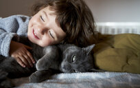 Portrait of happy toddler girl cuddling grey cat lying on bed - GEMF02921