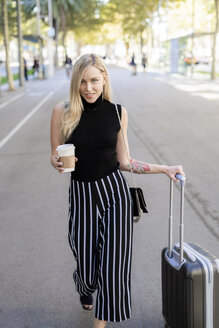 Portrait of smiling blond woman with coffee to go and wheeled luggage walking on street - GIOF06212
