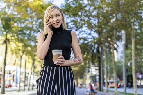 Portrait of smiling blond woman with coffee to go on the phone - GIOF06218