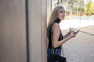 Young blond woman with coffee to go and cell phone leaning against wall looking at distance - GIOF06224
