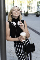 Portrait of happy blond woman with coffee to go, shoulder bag and headphones - GIOF06230