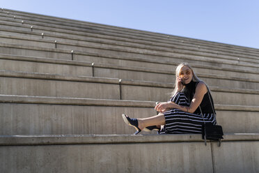 Blond young woman on the phone sitting on stairs outdoors - GIOF06242